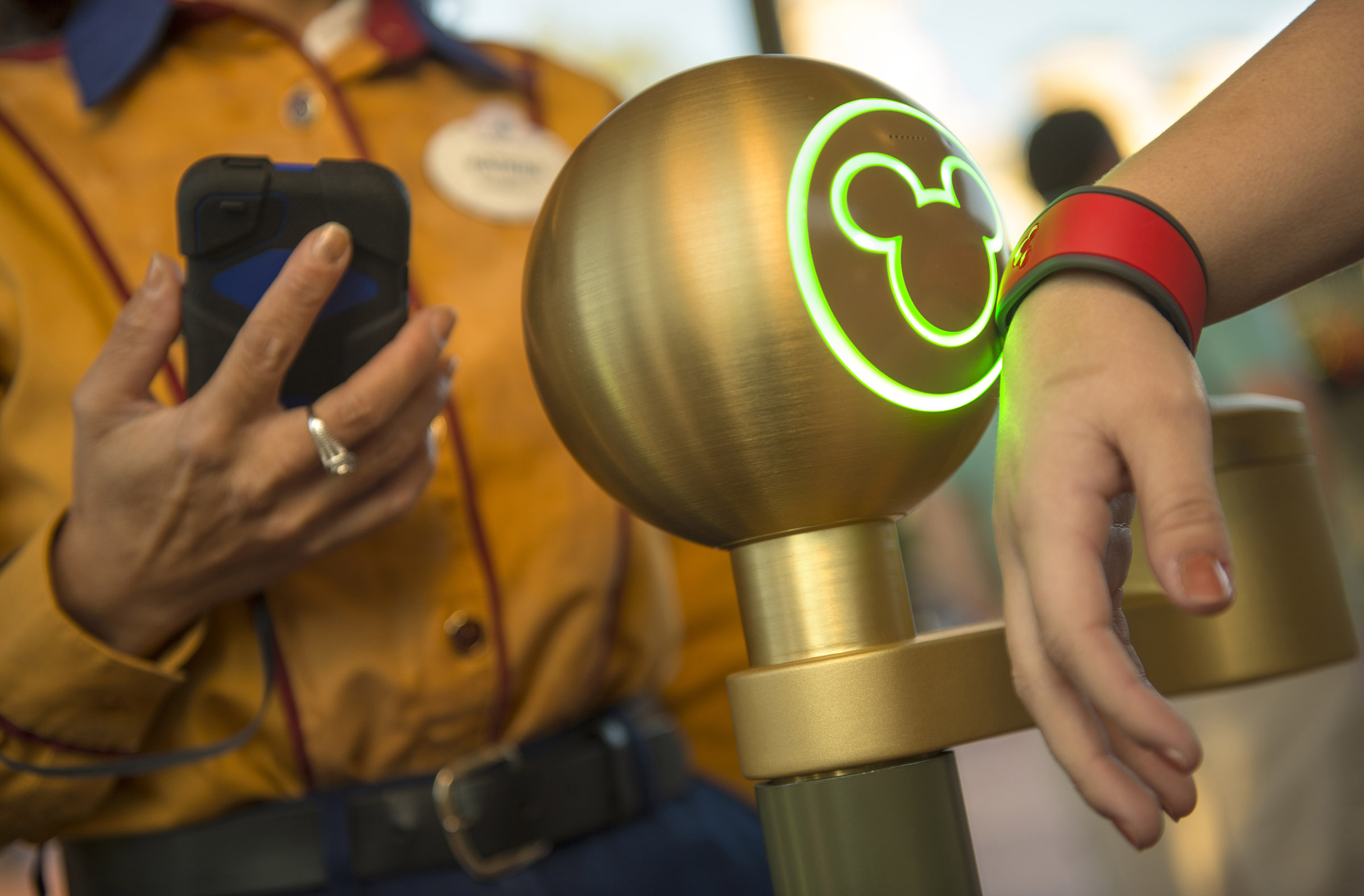 A Walt Disney World Resort guest uses a MagicBand to enter Magic Kingdom theme park in Lake Buena Vista, Fla. Guests also can use MagicBands to enter their Disney Resort hotel room, buy food and merchandise, enter Walt Disney World Resort theme parks and water parks, access their selected FastPass+ experiences and connect to Disney's PhotoPass. MagicBands are part of the new MyMagic+, which has the ability to connect nearly all aspects of the guest vacation experience at Walt Disney World Resort. (Kent Phillips, photographer)