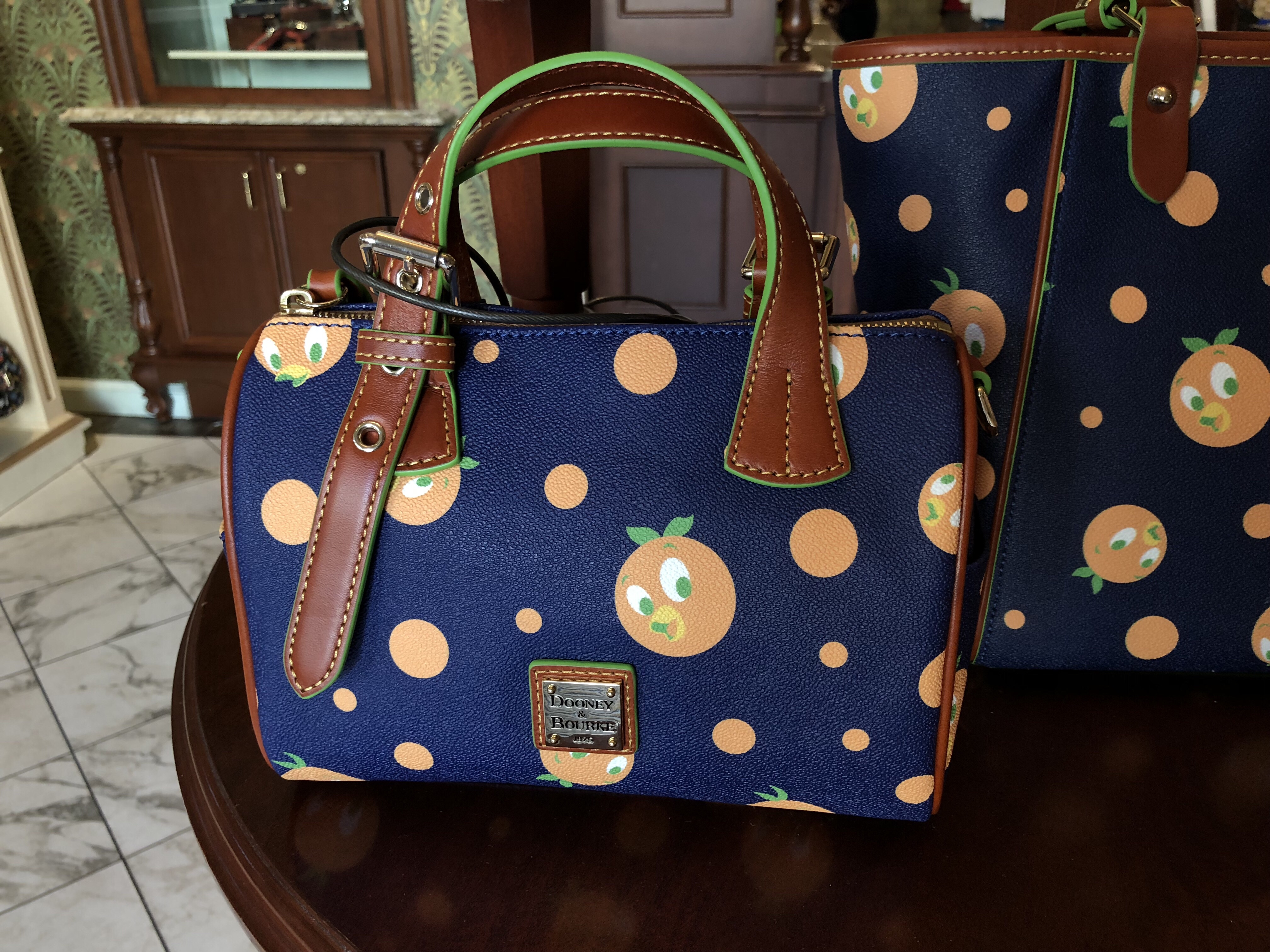 Dooney Bourke Embossed Metal Label On Front Part Of The Orange Bird Collection By